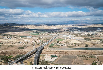 Lorca, Murcia / Spain - 29 Jan 2018: Aerial view north of the Castle (Castillo de Lorca). Two dual carriageways join up in a Y shape to become the A7. The distant Sierra Espuna mountains under cloud.