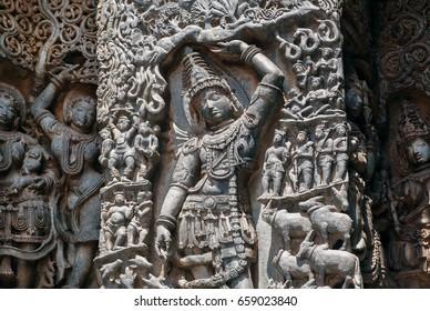 Lord Krishna lifting Mt. Govardhan on relief of the 12th century ornate Hoysaleshwara temple in Halebidu, India.