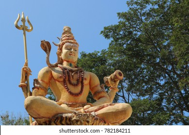Lord Siva with a trident and a drum against the sky and above the trees.