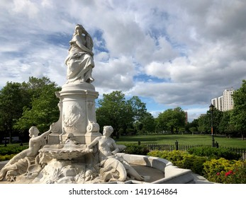Lorelei Fountain (also known as the Heinrich Heine Memorial) in Joyce Kilmer Park on a spring day with cloudy blue skies in The Bronx, New York