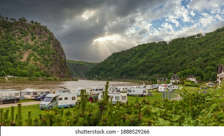 Loreley, Germany - May 24, 2019: Caravans and recreational vehicles camp on the banks of the Rhine River in the Rhine River Gorge opposite the historical Loreley Statue.