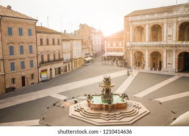 Loreto, Ancona, Italy - 11.10.2018: Square of Loreto, Basilica della Santa Casa in sunny day, portico to the side, people in the square in Loreto in Ancona, Italy