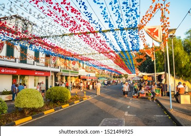 Loreto, Madeira, Portugal - Sep 7, 2019: Beautiful colorful street decoration during the celebration of the religious festival. Paper flowers hanging in the air. People celebrating, stalls with food.