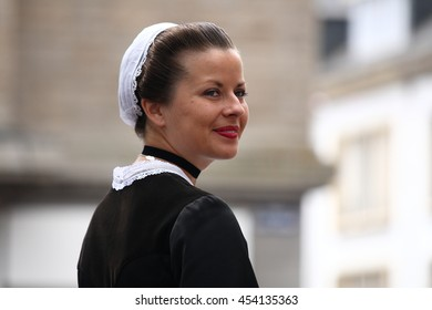 LORIENT, FRANCE - AUGUST 5, 2012: Young woman wearing traditional breton costume and embroidered lace headdress participates Interceltique festival in Lorient, french Brittany on the 5th August 2012.