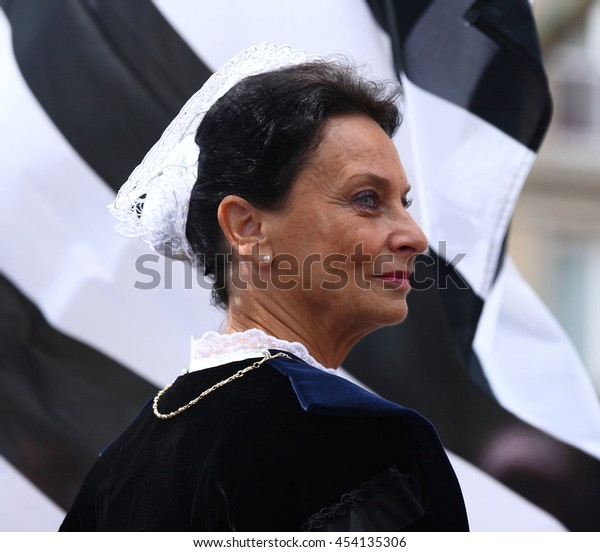 LORIENT, FRANCE - AUGUST 5, 2012: Woman wearing traditional breton costume near the flag of Brittany participates Interceltique festival in Lorient, french Brittany on the 5th August 2012.