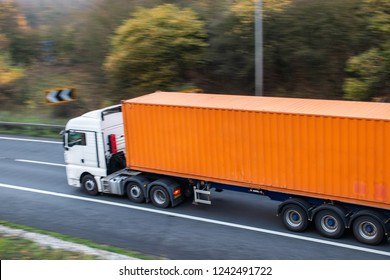 Lorry with orange shipping container in motion on the road