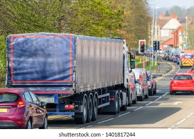 lorry truck stuck in busy traffic on road in british town at noon time