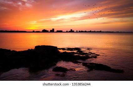 Los Alcazares, Region of Murcia, Spain. Amazing sunrise at seaside with sun reflection on water. Sunset of the Mar Menor on the sleeve, Spain. La Manga del Mar Menor Skyline. Beautiful beach in town.