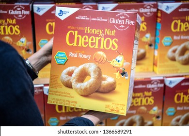 Los Angeles, 04/09/2019 Customer hand holding a family size package of Honey Nuts Cheerios Brand cereal in a supermarket aisle