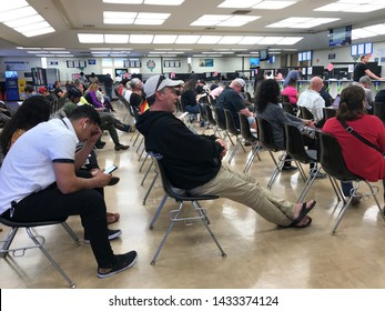 LOS ANGELES, April 25, 2019: DMV Department of Motor Vehicles Culver City. Long rows of chairs with people sitting, waiting their turn, inside the busy waiting room area.