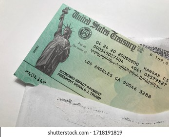 LOS ANGELES, April 28th, 2020: United States Treasury Economic Impact Payment stimulus check for Coronavirus COVID-19 relief. Close up with check sticking out of envelope.