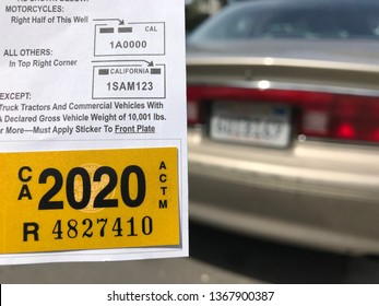LOS ANGELES, April 8th, 2019: Close up of a new yellow DMV 2020 car registration sticker next to the license plate of a blurry brown older Buick, parked on a residential street, in the background.