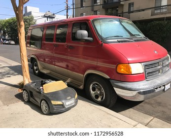 LOS ANGELES, Aug 26, 2018: An electric kid car Audi stands parked next to a regular-sized adult car on a sidewalk in Hollywood, California.