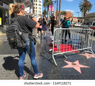 LOS ANGELES, AUG 30, 2018: Woman photographing barricades surrounding President Donald Trump's star on the Hollywood Walk of Fame, near Hollywood Boulevard and Highland. It was vandalized on July 25.