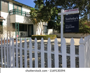 LOS ANGELES, AUG 30, 2018: A For Lease and real estate sign from Sotheby's behind a white picket fence on an idyllic property in Hollywood, California.