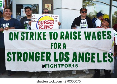 LOS ANGELES, CA   APRIL 15, 2015: Protesting fast food workers hold a banner advocating raising the minimum wage for fast food workers during a demonstration in Los Angeles on April 15, 2015.