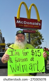 LOS ANGELES, CA   APRIL 15, 2015: A protestor stands near a McDonald's sign, holding a sign advocating raising the minimum wage at Walmart during a demonstration in Los Angeles on April 15, 2015.