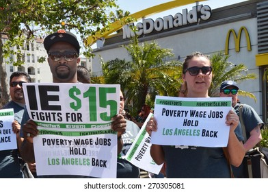 LOS ANGELES, CA   APRIL 15, 2015: Two protestors hold signs advocating raising the minimum wage in front of a McDonald's restaurant during a demonstration in Los Angeles on April 15, 2015.