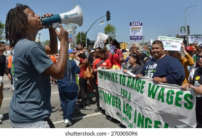 LOS ANGELES, CA  APRIL 15, 2015: A man shouts into a megaphone at protestors holding a banner advocating raising the minimum wage during a demonstration in Los Angeles on April 15, 2015.