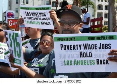 LOS ANGELES, CA   APRIL 15, 2015: Protestor hold signs advocating raising the minimum wage at during a rally in Los Angeles on April 15, 2015.