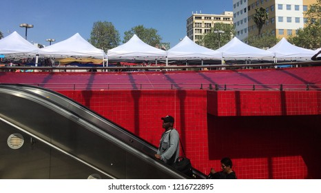 LOS ANGELES, CA, APRIL 2017: man and woman riding escalator up, past red tiled wall, from the Westlake/MacArthur Park LA Metro subway station. Market tents in background