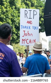"LOS ANGELES, CA - AUGUST 26, 2018:  A protester at the Unite for Justice rally holds a sign reading ""RIP and thank you John McCain"""