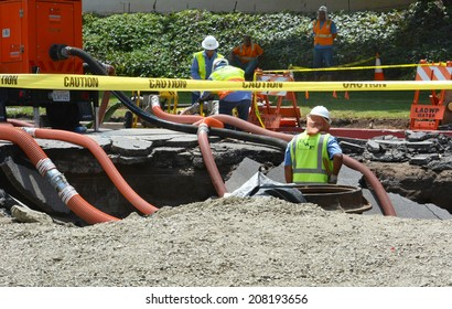 LOS ANGELES, CA - JULY 30, 2014: Workers work in a sink hole to fix a 93 year old broken water main which spilled 20 million gallons of water, flooding parts of West Los Angeles and the UCLA campus.