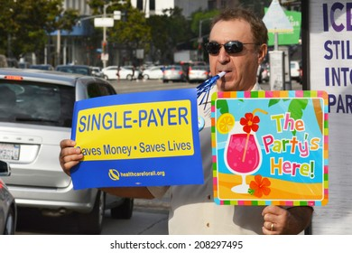 LOS ANGELES, CA - JULY 30, 2014: A demonstrator, holds two signs celebrating the 49th birthday of Medicare and advocating single payer healthcare reform during a rally in Los Angeles on July 20, 2014.