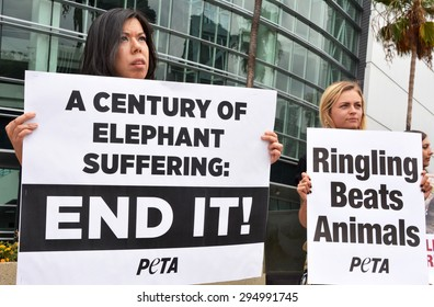 LOS ANGELES, CA â?? JULY 9, 2015: Two protestors stand in front of the Staples Center in Los Angeles holding signs protesting the treatment of elephants by Ringling Bros. Circus on July 9, 2015.