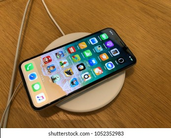 Los Angeles, CA: March 16, 2018: An Iphone X on a wireless charger at an Apple store. The Iphone 8, 8S and Iphone X are the first Apple phones that support wireless charging.