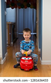 Los Angeles, CA - March 29, 2014: 3 year old sitting on Lightning McQueen car character from the Cars movie, inside the house.