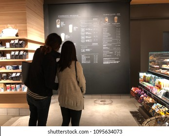Los Angeles, CA: May 20, 2018: Two women looking at a Starbucks Reserve menu in Los Angeles.   Starbucks has plans to open several hundred Starbucks Reserve stores in the world.