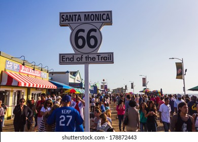 LOS ANGELES, CA -  MAY 27, 2013: People walking by Santa Monica end of famous Route 66 in Santa Monica Pier