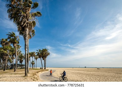 LOS ANGELES, CA - MAY 30: Two visitors cycling on the beachfront at Venice Beach Beach, CA on MAY 30, 2015.  Venice Beach is one of California's most popular visitor attractions.
