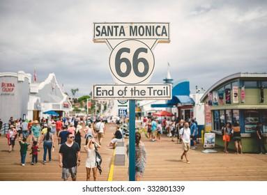 LOS ANGELES, CA - SEP 12, 2015: People walking by Santa Monica end of famous Route 66 in Santa Monica Pier