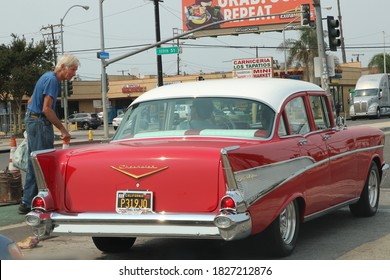Los Angeles, CA Sept 12, 2020 A homeless man talks to a classic car driver at stoplight.