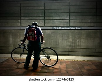 LOS ANGELES, CA, SEPT 2016: man wearing backpack waits with bicycle for LA Metro train on the platform at 7th Street Metro Center in Downtown