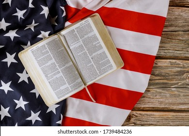 Los Angeles CA US 16 MAY 2020: Open is reading Holy Bible book with prayer for america over ruffle American flag on wooden table