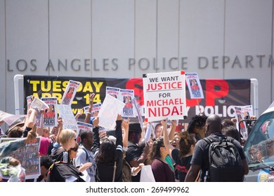 Los Angeles, CA, USA - April 14, 2015:  People with raised signs in front of Los Angeles Police Department during Stop Murder by Police. Protest against murdering of black and latino people by police.