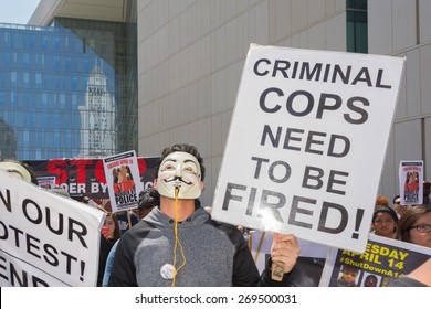 Los Angeles, CA, USA - April 14, 2015:  Man wearing mask holding a sign during Stop Murder by Police. Protest against the brutalization and murdering of black and latino people by police.
