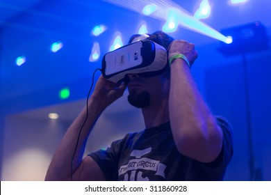 Los Angeles, CA - USA - August 29, 2015: Guy tries virtual glasses headset during VRLA Expo, virtual reality exposition, event at the Los Angeles Convention Center in Los Angeles.