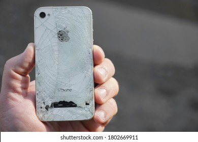Los Angeles, CA, USA - December 07, 2019: Broken Apple iPhone with cracked screen on gray background, selective focus