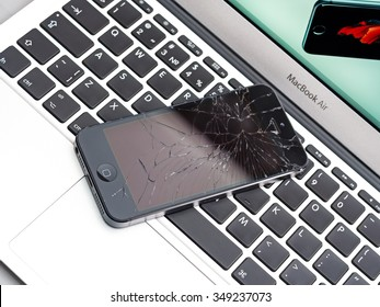Los Angeles, CA, USA - December 07, 2015: Broken Apple iPhone with cracked screen on Apple MacBook Air laptop