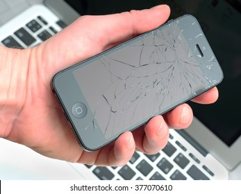 Los Angeles, CA, USA - December 07, 2015: Man holds in his hand broken Apple iPhone with cracked screen