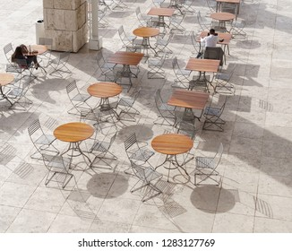Los Angeles, CA, USA - January 8, 2019: People relaxing at outdoor dining area at Getty Center museum. Shadow of tables and chairs on stone tile floor. Overhead view.