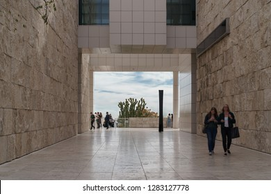 Los Angeles, CA, USA - January 8, 2019: Outdoor walkway to the cactus garden at Getty Center museum. Sky and clouds background. Blurred motion of people walking.
