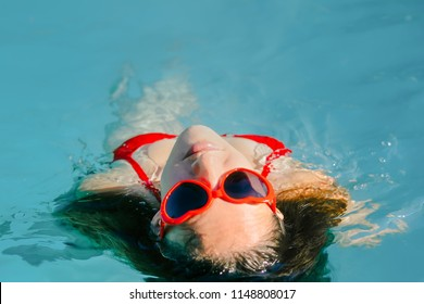 Los Angeles, CA / USA - July 4th, 2017: Brunette girl swimming in pool with red bikini and red heart shaped sunglasses in summer time