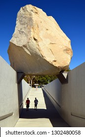 Los Angeles, CA, USA July 24, 2014 Two young men stand under Levitated Mass, a sculpture by Michael Heizer, at the Los Angeles County Museum of Art
