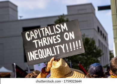 Los Angeles, CA / USA - June 17, 2020: Protester holding a 'Capitalism Thrives on Inequality' sign  at the Black Lives Matter Los Angeles protest again District Attorney Jackie Lacey