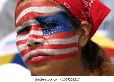 Los Angeles, CA, USA- May 01, 2006; A Mexican woman's face is painted with an American flag as she marches during  'A Day Without an Immigrant' , more than 500,000 people marched through LA streets.
